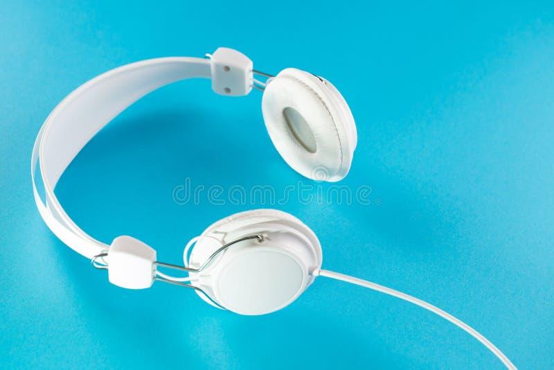 Белые наушники при кабель изолированный на голубой предпосылке стоковая фотография