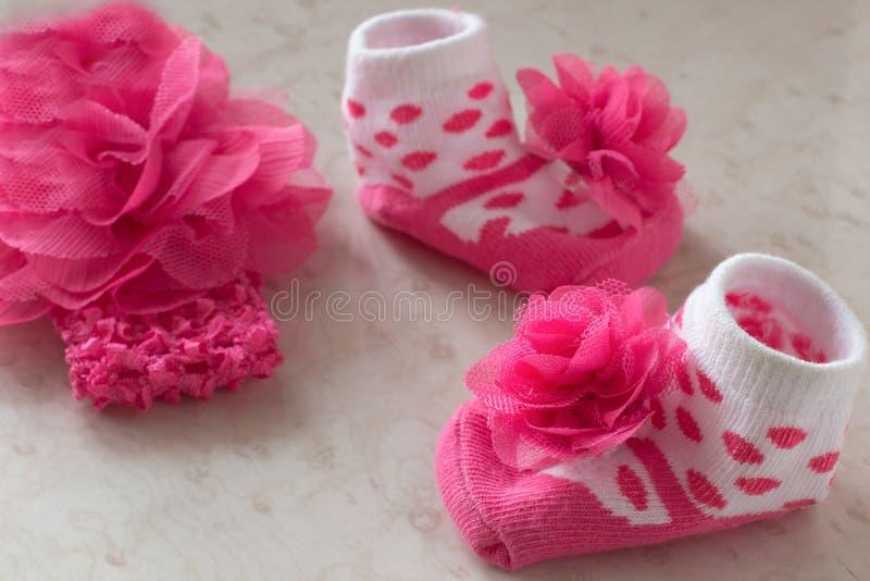 Белые носки в розовых точках польки и цветок для младенца на tabl стоковая фотография rf