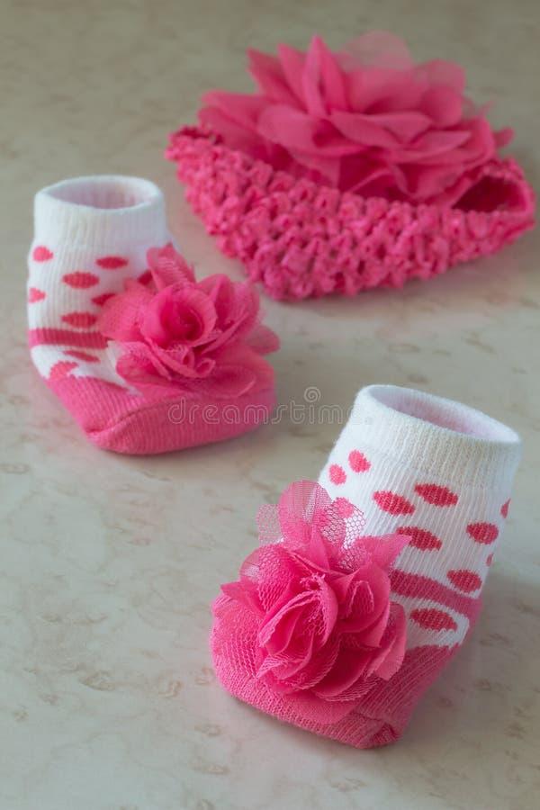 Белые носки в розовых точках польки и цветок для младенца стоковое фото