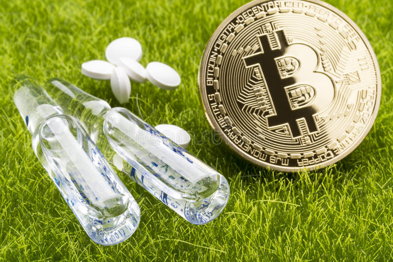 Белые пилюльки и ampules с bitcoin чеканят на предпосылке травы - концепции цены здравоохранения стоковые изображения rf