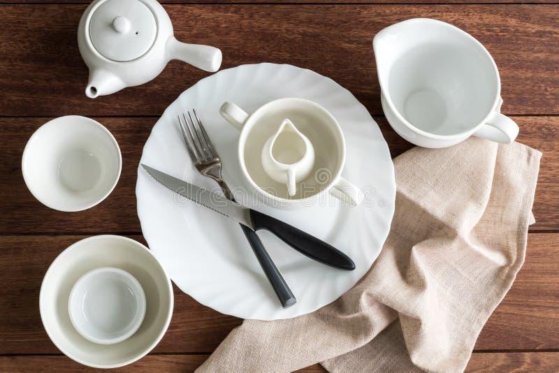 Белые пустые блюда на деревянном столе с космосом экземпляра стоковое фото