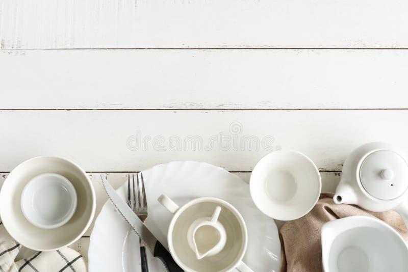 Белые пустые блюда на деревянном столе с космосом экземпляра стоковое изображение