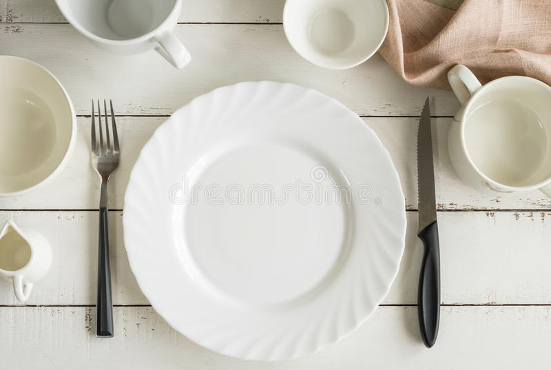 Белые пустые блюда на деревянном столе с космосом экземпляра стоковые фотографии rf