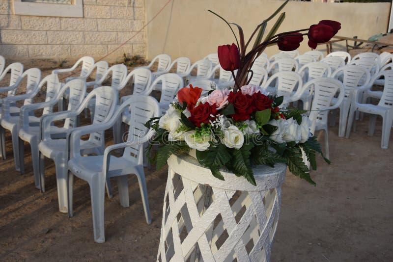 Белые пластичные стулья в ряд и букет роз для свадьбы стоковые изображения rf