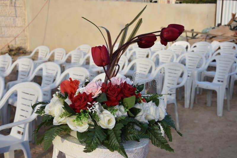 Белые пластичные стулья для свадьбы и букет цветков шарлаха и белых стоковое изображение