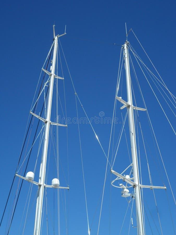 Белые рангоуты яхты против ясного голубого неба стоковое изображение rf