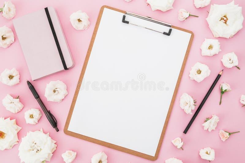 Белые розы цветут с доской сзажимом для бумаги, тетрадью и ручкой на розовой предпосылке Плоское положение, взгляд сверху Женская стоковое изображение