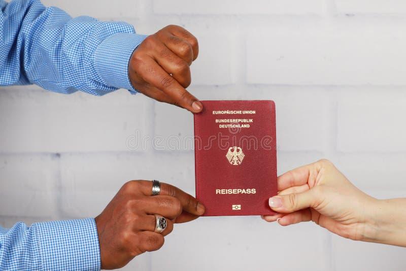 Белые руки и шайки бандитов держа немецкий пасспорт стоковая фотография