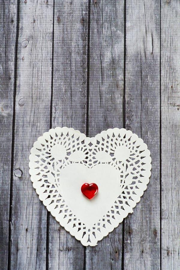 Белые сердца doily с красным сердцем на деревянной предпосылке стоковое фото rf