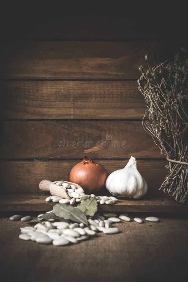 Белые фасоли с тимианом и chorizo на деревянном столе стоковое изображение rf