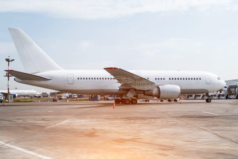 Белый большой самолет в автостоянке на авиапорте стоковое фото rf