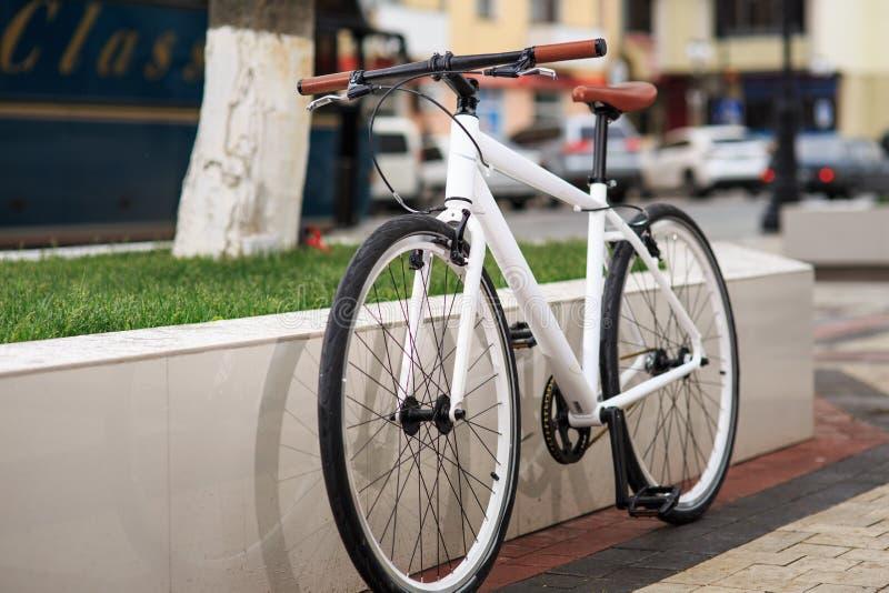 Белый велосипед фиксированн-шестерни на улице стоковое фото rf