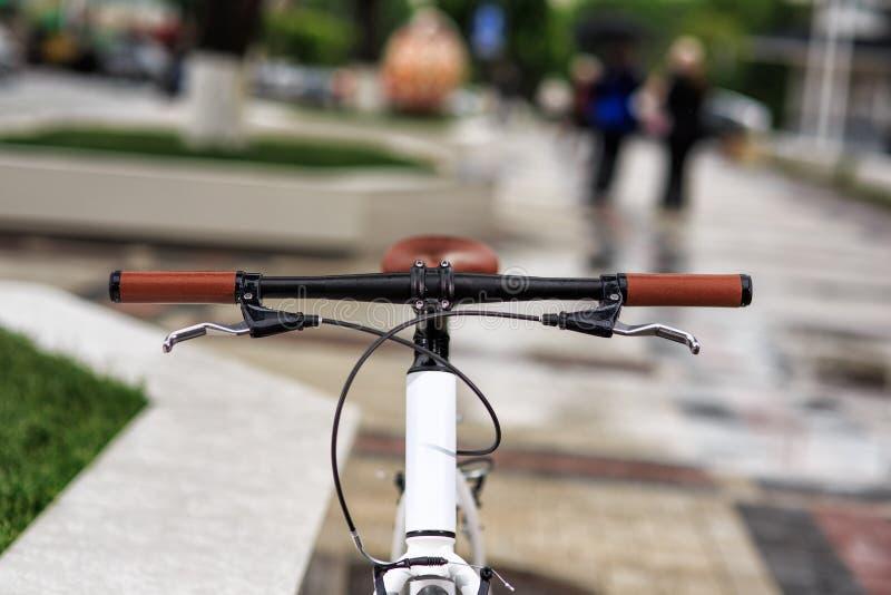 Белый велосипед фиксированн-шестерни на улице стоковое фото