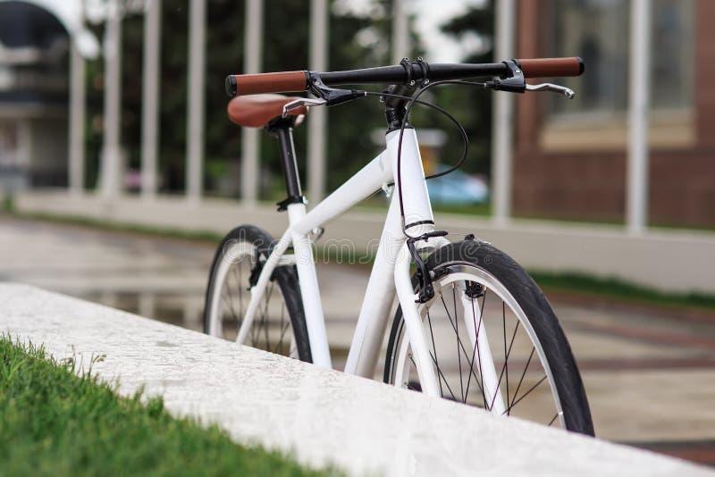 Белый велосипед фиксированн-шестерни на улице стоковые фото
