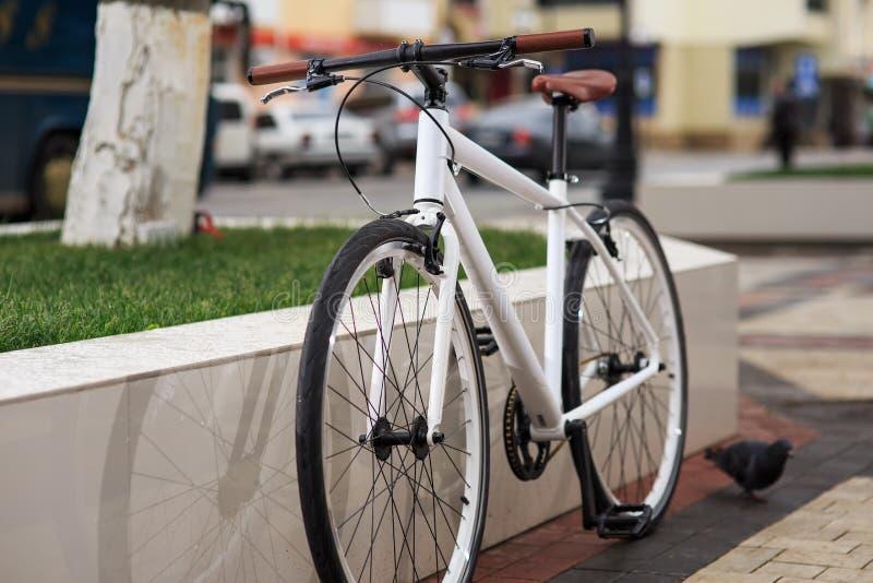 Белый велосипед фиксированн-шестерни на улице стоковое изображение