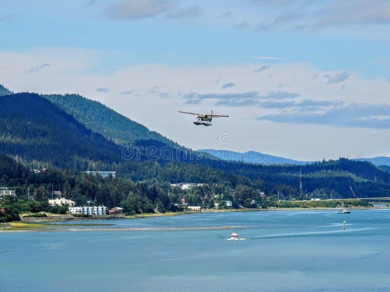 Белый гидросамолет понтона поплавка принимая от гавани Juneau стоковые фотографии rf
