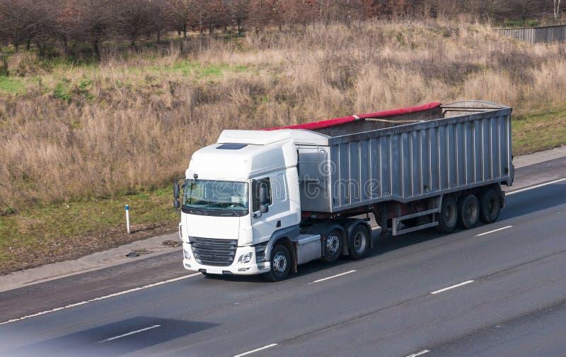 Белый грузовик с трейлером в движении на шоссе стоковое фото rf