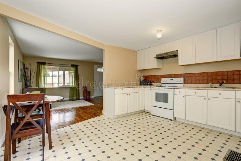Белый интерьер комнаты кухни с плиточным полом и комплектом обеденного стола стоковые изображения