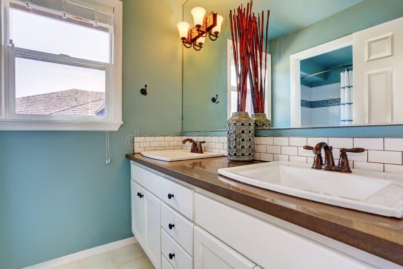 Белый и голубой интерьер ванной комнаты с 2 раковинами стоковое изображение