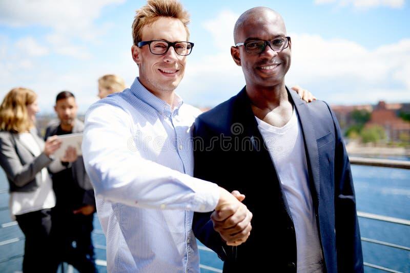Белый коллега и черный коллега тряся руки стоковое изображение rf