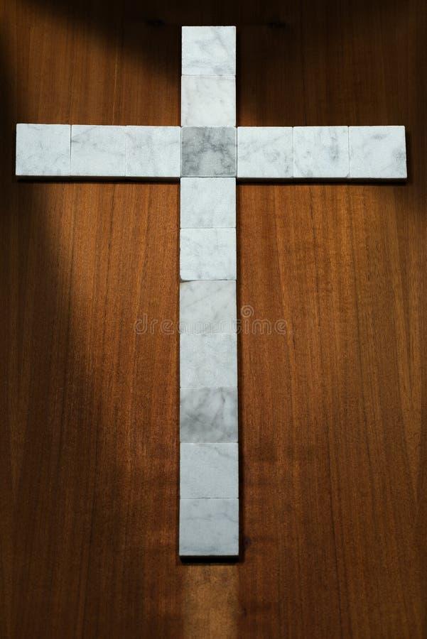 Белый мраморный крест на деревянной предпосылке стоковая фотография rf