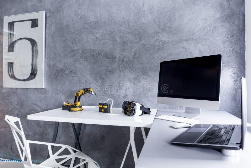Белый настольный компьютер с робототехническими игрушками в современной комнате стоковое изображение