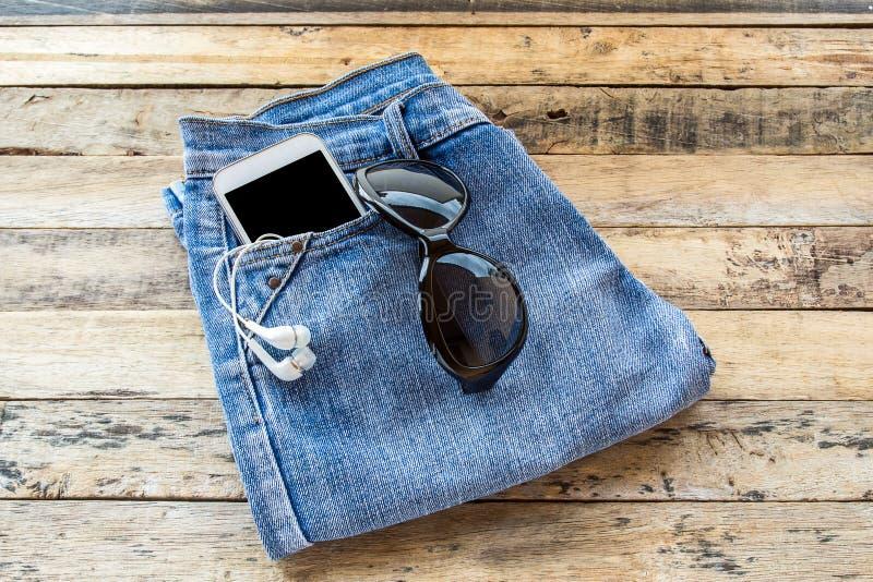 Белый наушник, солнечные очки, умный телефон и голубые джинсы на деревянном t стоковая фотография rf