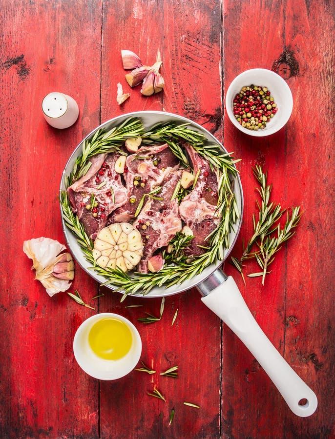 Белый лоток с сырцовой поясницей овечки прерывает мясо, травы, масло и специи на красной деревянной предпосылке стоковые фото