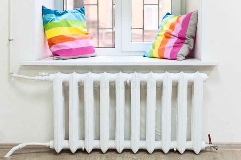 Белый радиатор центрального отопления в отечественной комнате под окном стоковое фото rf