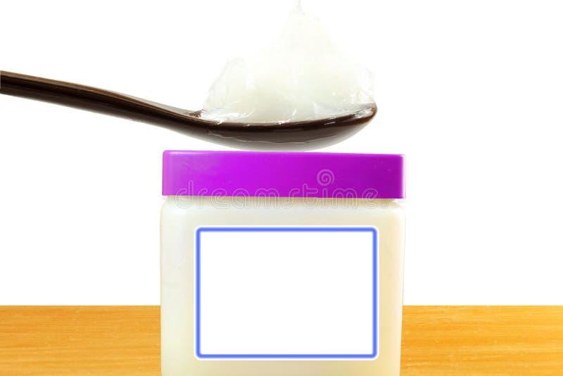 Белый студень нефти в ложке с опарником в белой предпосылке стоковое фото