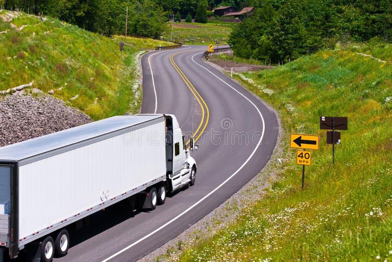 Белый трейлер тележки на извилистой дороге между зелеными холмами стоковое изображение rf