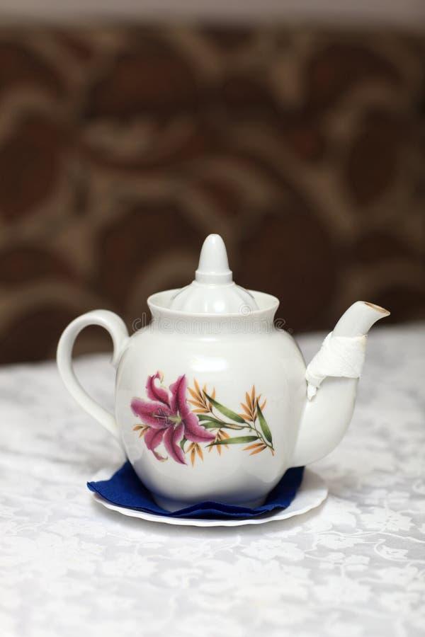 Белый чайник с флористическим орнаментом стоковое фото