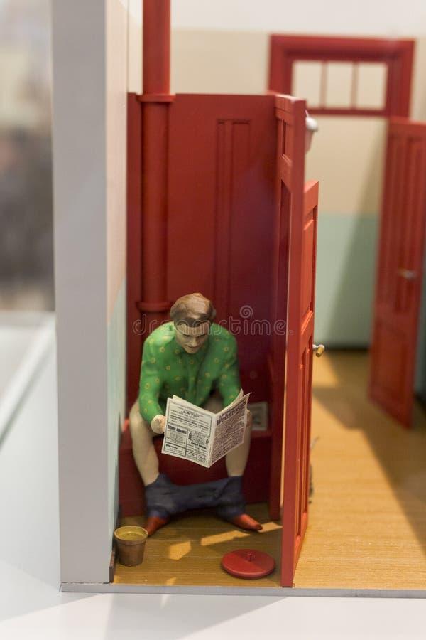 Белый человек на туалете прочитал газету стоковое фото rf