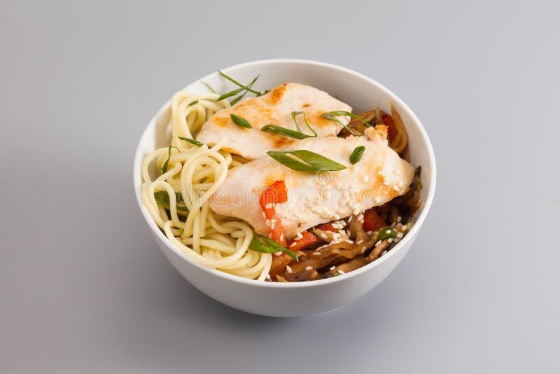 Белый шар лапшей с частью мяса и овощей жареной курицы блюдо на серой предпосылке, конце-вверх стоковые фотографии rf
