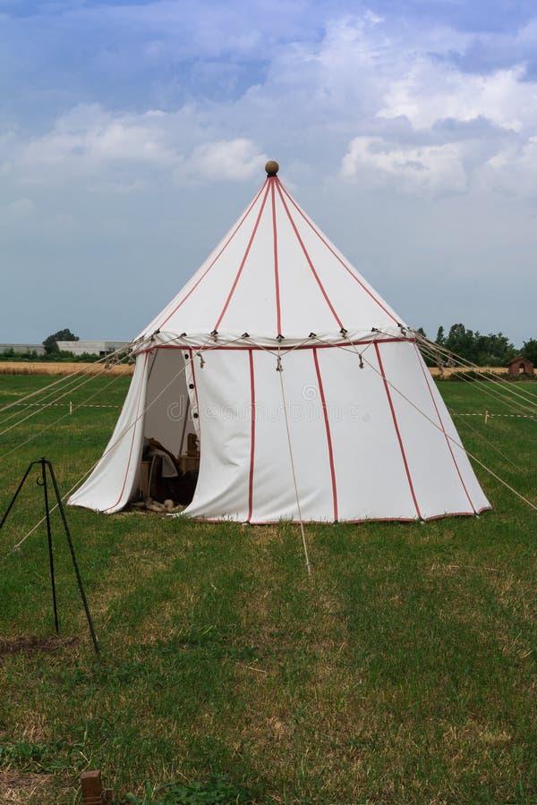 Белый шатер и деревянная тренога для костра на луге стоковое фото rf