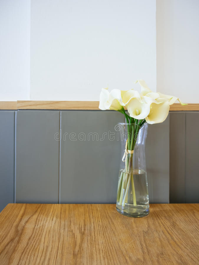 Белый Calla Lilly цветет в стеклянной вазе на таблице стоковая фотография