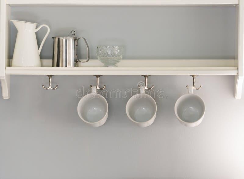 3 белых кофейной чашки вися в ряд кувшин и стеклянное усаживание стоковая фотография