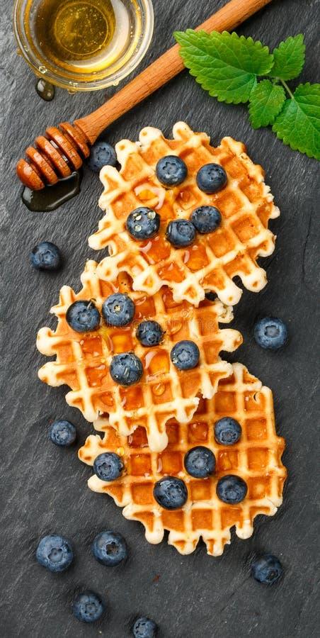 Бельгийские waffles с медом и свежими ягодами голубикой и мятой стоковая фотография rf