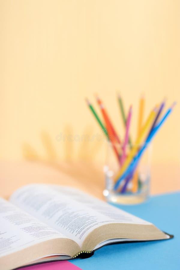 Библия и набор покрашенных карандашей готовых для исследования стоковое изображение