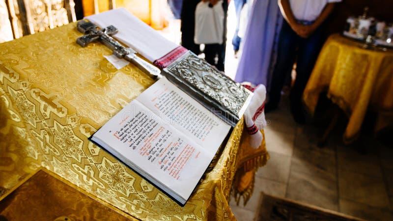 Библия на чтени-столе, священном аналое в церков украшенной с золотыми фризами и орнаментах, открытой книге - Евангелии в старом  стоковые изображения