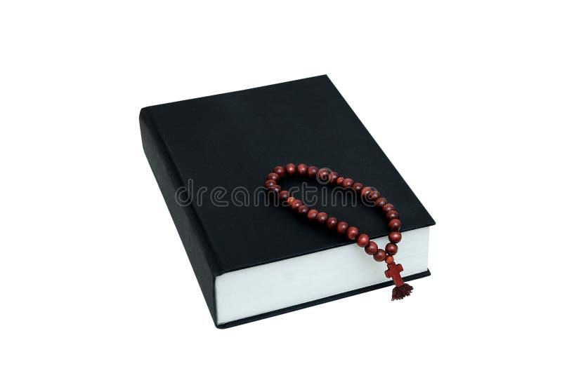 Библия черной книги и деревянный розарий с крестом стоковые изображения