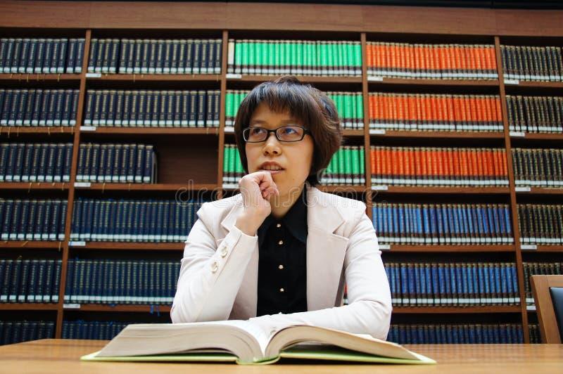 Библиотека, книжные полки, чтение, думая  стоковое изображение rf