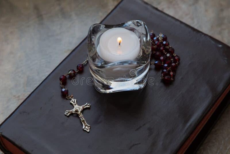 Библия с розарием и свечой стоковые изображения rf