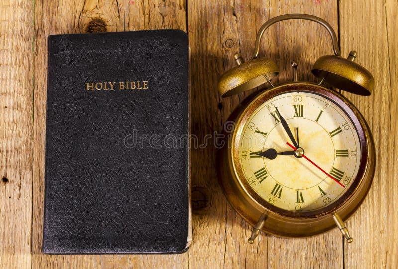 Библия с часами на древесине стоковое изображение rf