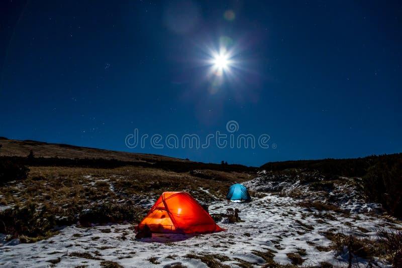 Бивуак спорта зимы пеший в ландшафте горы на ноче с ярким полнолунием стоковая фотография rf