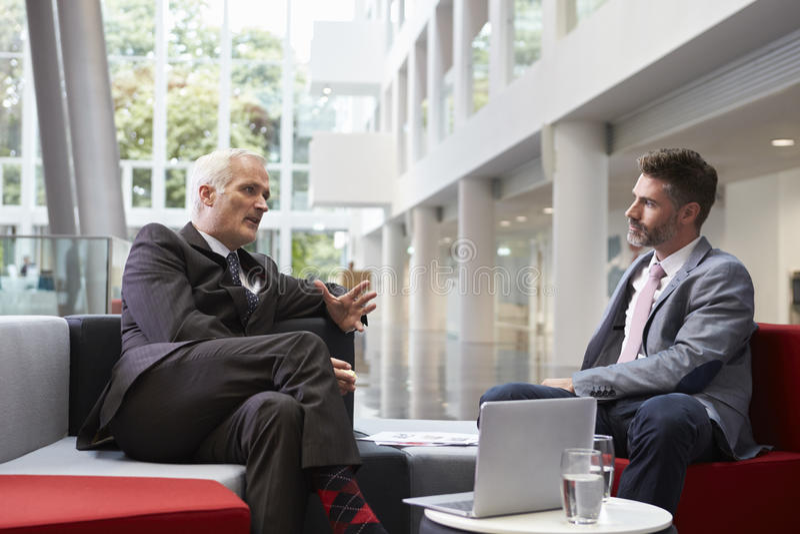 2 бизнесмена встречая в зоне лобби современного офиса стоковое фото