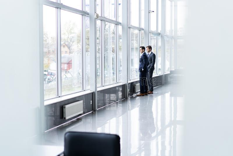 2 бизнесмена имея неофициальное заседание в коридоре офиса стоковое изображение