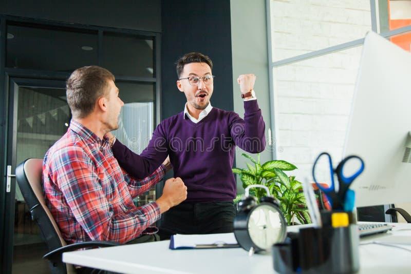 2 бизнесмена празднуют победу, достигаемость цели, студентов на светлой комнате стоковая фотография
