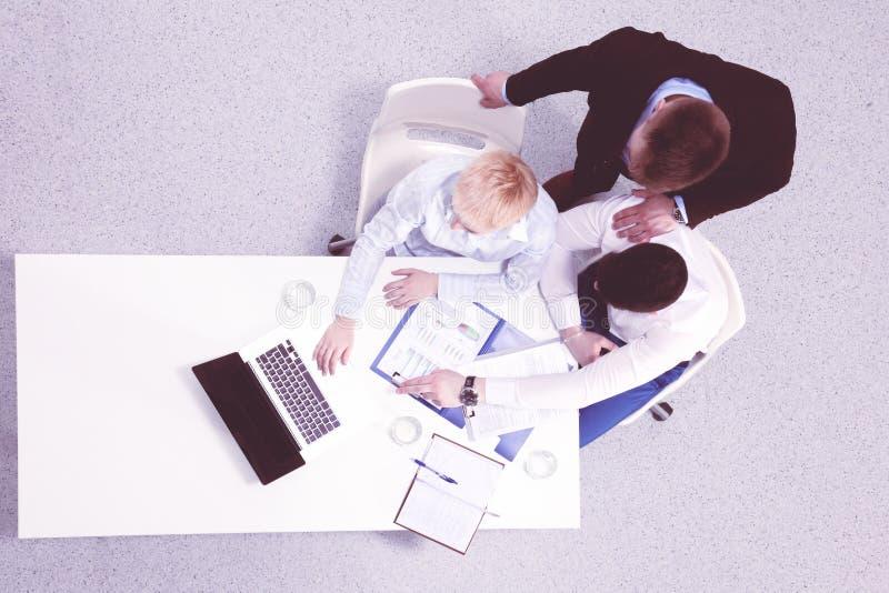 2 бизнесмена сидя на их столе с ноутбуком r стоковая фотография
