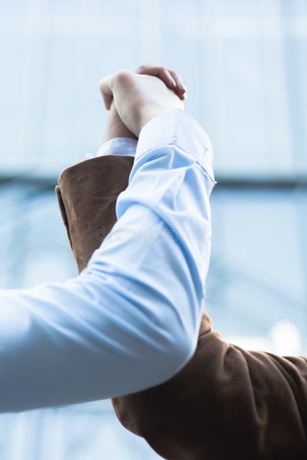 2 бизнесмена схватывая руки совместно стоковое изображение